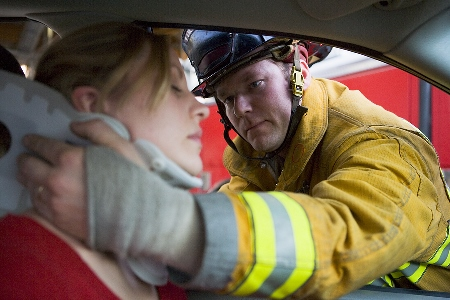 Firefighter helping a young women in a motor vehicle accident