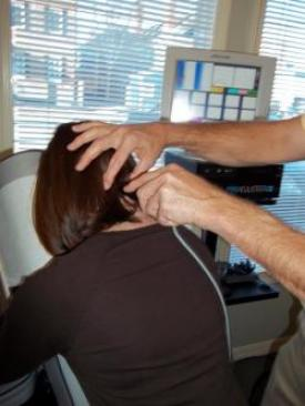 Woman getting Pro-Adjuster treatment for her neck pain.