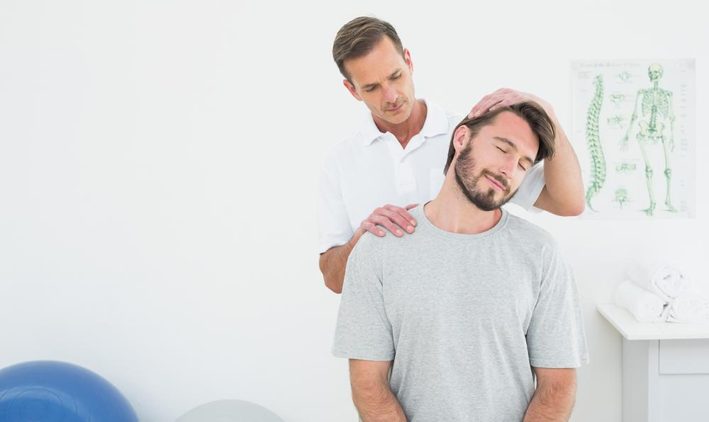 Man with neck pain getting his neck looked at by a chiropractor.