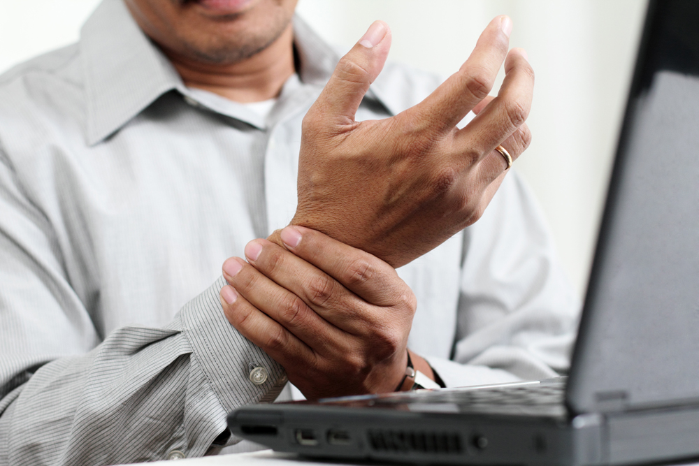 man suffering from carpal tunnel syndrome in his office