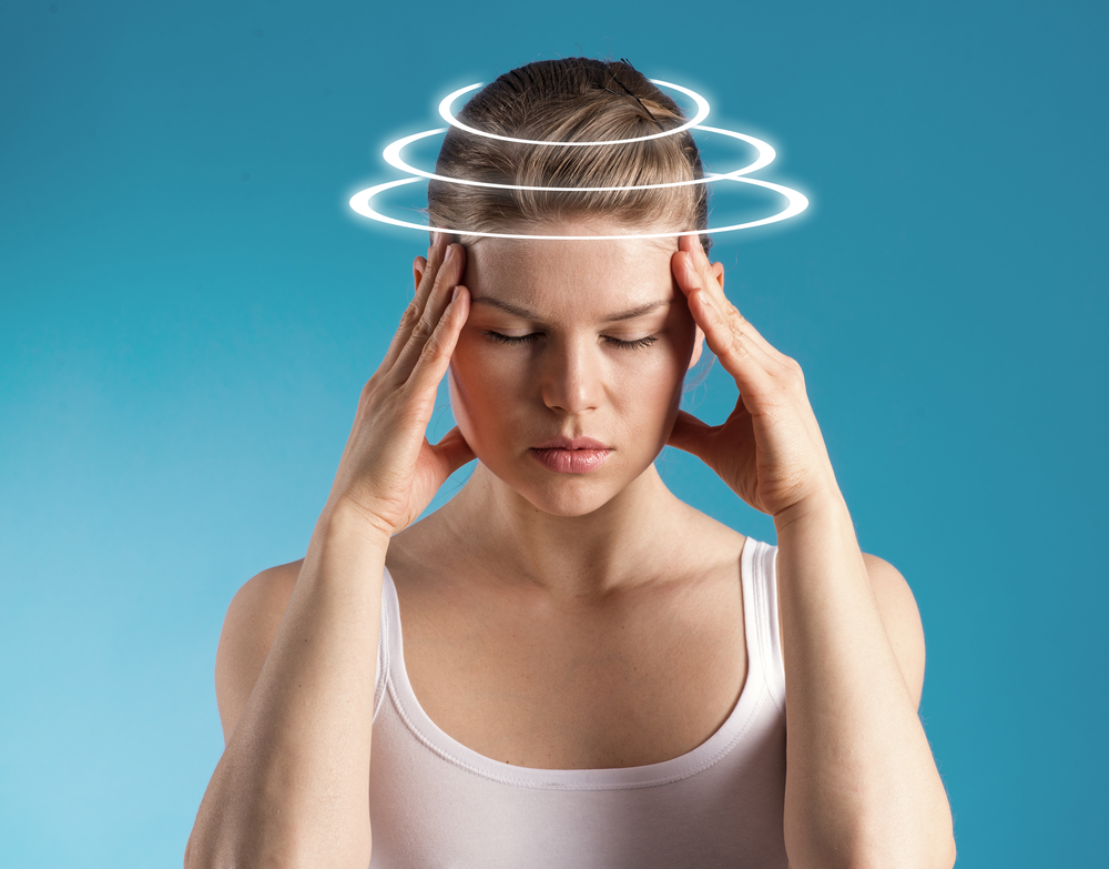 woman holding her head from migraine pain who needs chiropractic treatments in Portsmouth
