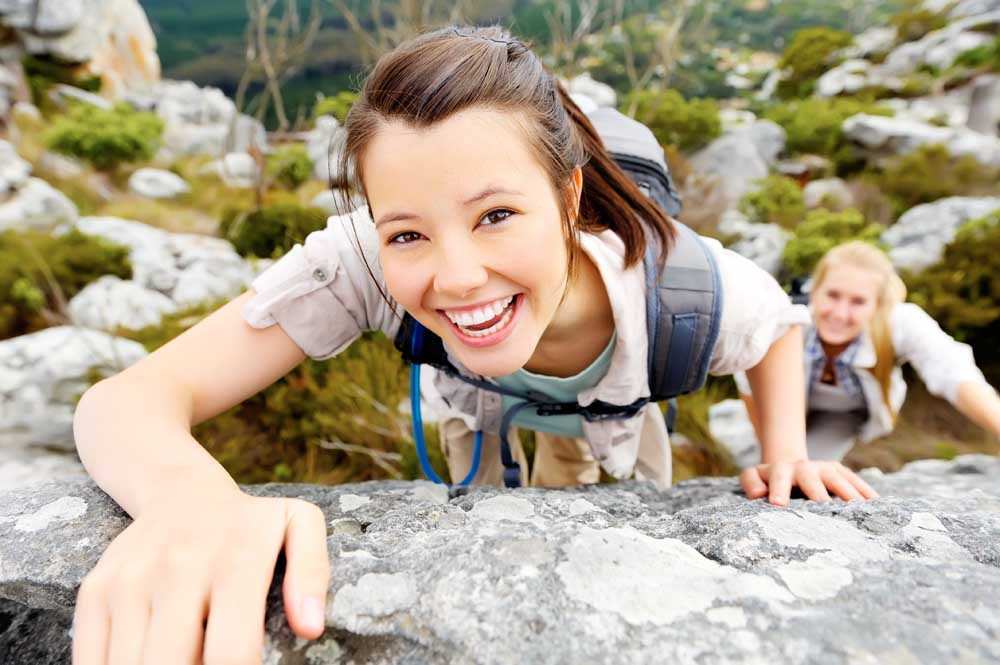 Woman happy about her life while mountain climbing.