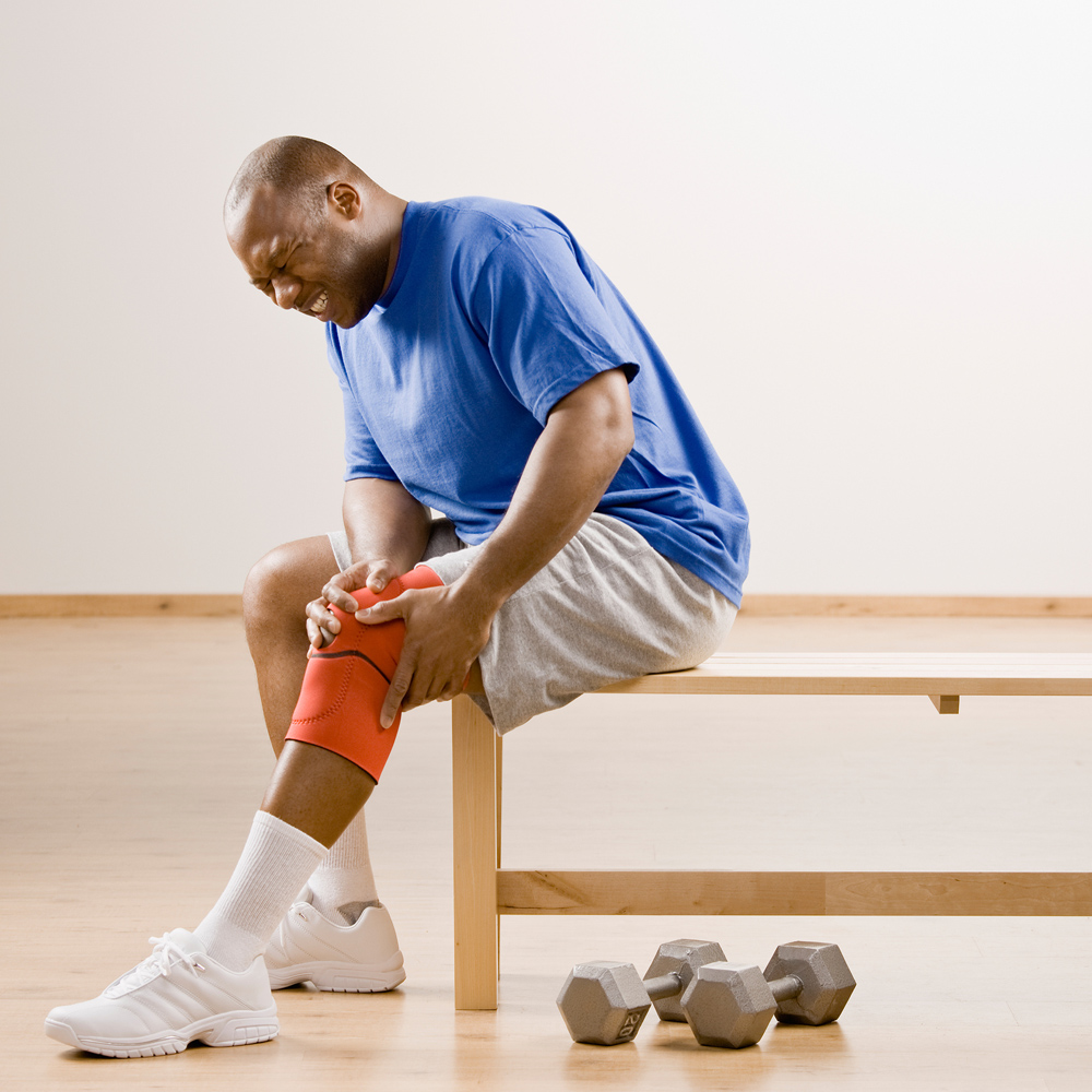 man suffering from knee pain after lifting weights