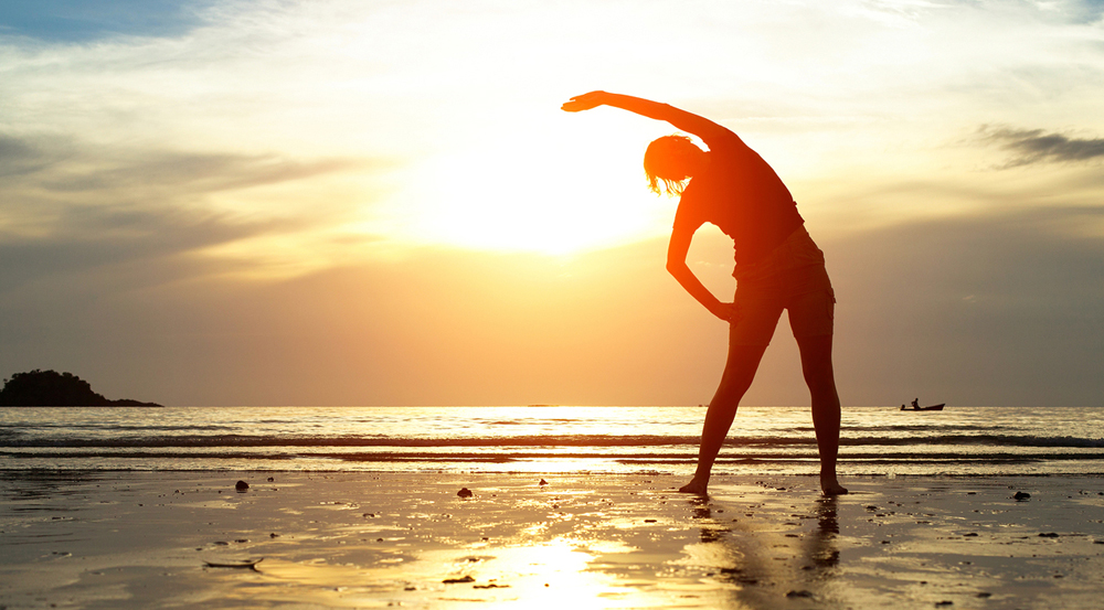 woman stretching at sunset on the beach after chiropractic care to relieve her back pain