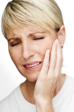 woman holding jawline in pain