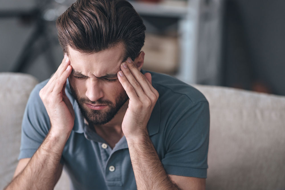 Man with a headache needs to seek chiropractic care in Sacramento.