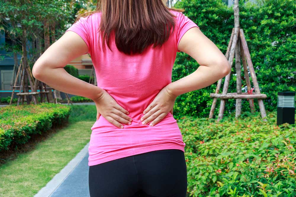 Woman in her garden experiencing lower back pain.